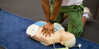 Person giving chest compressions to a CPR dummy