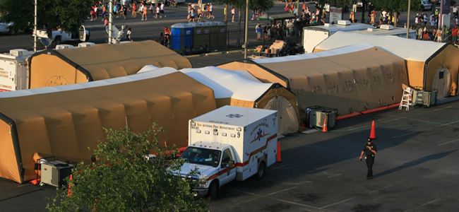 An ambulance backs up to a series of medical tents