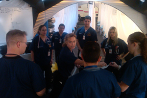A female nurse briefs her team of male and female nurses in a medical tent