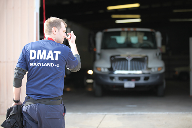 DMAT personnel directs truck pulling out of a garage.