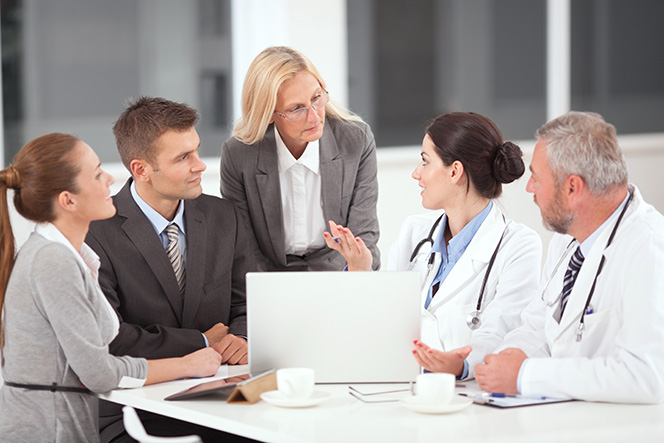 Businesswoman holding meeting with doctors and other business associates
