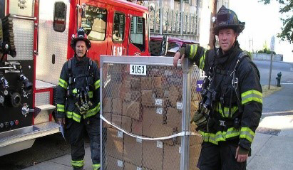 Two firefighters standing next to a CHEMPACK shipment