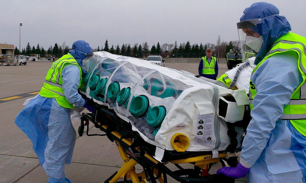 A mock patient is being transported from the aircraft to an ambulance destined for the Regional Ebola and Other Special Pathogen Treatment Center at the University of Minnesota Medical Center as part of the Tranquil Shift exercise.